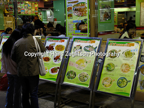Women looking at the chinese Menu in front of a restaurant in Kowloon.