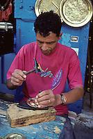 Tunisia, Sidi Bou Said.  Souvenir Vendor Tapping Designs into Brass Trays.