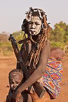 Mursi mother with her children and Kala?nikov rifle in Omo valley village Ethiopia