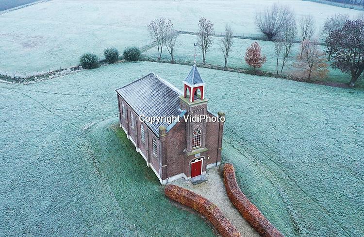Foto: VidiPhoto<br /> <br /> HOMOET – En toen was Nederland opeens wit. In de Betuwe zelfs spierwit maandagmorgen, dankzij de eerste –en voorlopig laatste- serieuze nachtvorst van deze herfst. Voor grote delen van ons land werd zelfs code geel afgekondigd vanwege gladheid. Aan de andere kant leverde het fotografisch mooie plaatjes op rond zonsopgang en net voordat mist op veel plekken het zicht flink terugbracht, zoals hier in het Betuwse buurtschap Homoet. Foto: Het vluchtheuvelkerkje (1869) van de Hervormde gemeente Valburg-Homoet staat op dit moment leeg. Vanwege de coronamaatregelen kunnen er op dit moment geen diensten worden gehouden. Tot maart was er iedere eerste zondag van de maand nog een kerkdienst.