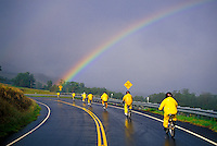 On a rainy day, an organized bike group rides toward a rainbow down Haleakala on Haleakala Crater Road through the Haleakala Ranch.