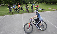 Caleb Leis of Bella Vista shows proper technique with a mountain bike to a group from Wisconsin Monday June 7, 2021 at Memorial Park in Bentonville. Leis and Rich Drew (not pictured) were teaching mountain bike skills through the Ride series MTB skills clinics. For more information see www.therideseriesmtb.com/rideseries Visit nwaonline.com/2100608Daily/ and nwadg.com/photo. (NWA Democrat-Gazette/J.T. Wampler)