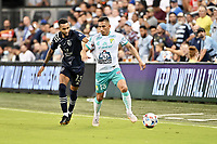 KANSAS CITY, KS - AUGUST 10: Angel Mena #13 Club Leon holds off Amadou Dia #13 Sporting KC during a game between Club Leon and Sporting Kansas City at Children's Mercy Park on August 10, 2021 in Kansas City, Kansas.