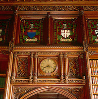 One of the clocks in the library is framed by elaborate wooden carving and little busts of kings and queens