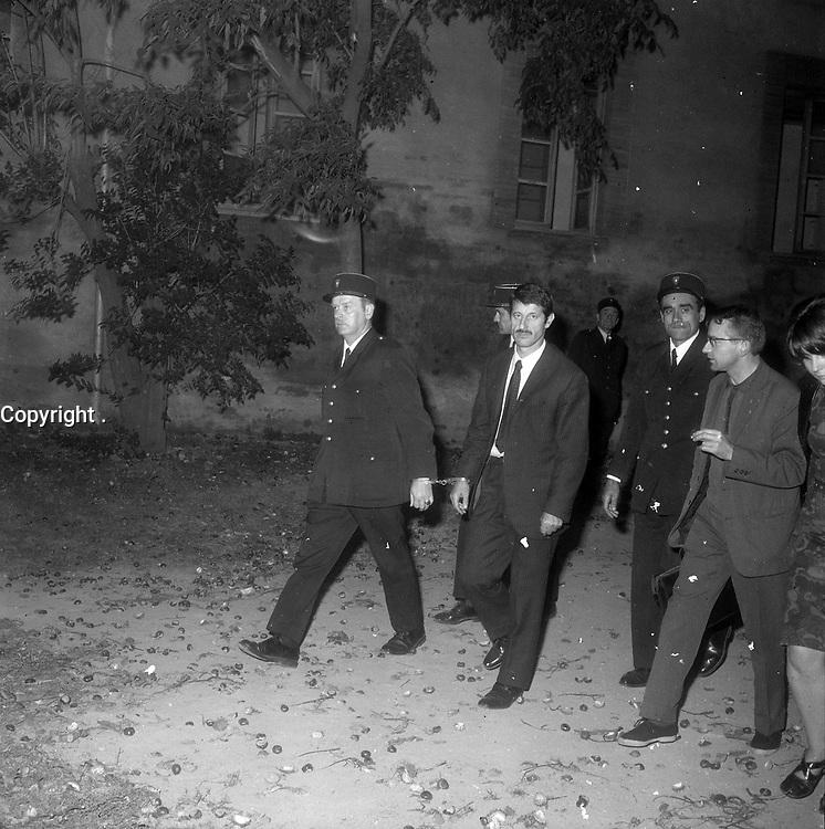 A l'extérieur du Palais de Justice. 6 octobre 1971. René Vignal menotté quittant le Palais (vue de 3/4 face), est entouré de policiers. Vue de nuit. Cliché pris à la fin du procès de René Vignal (ancien footballeur), accusé d'une série de braquages perpétués à Toulouse et dans la région bordelaise entre 1969 et 1970. Observation: Au côté de René Vignal, comparaissaient également MM. Francis Bataille, Roger Claverie, Roger Martin, Marcel Filiol, Jean-Pierre Arrou, Guy Martin, René Doncel et Jean-Louis Parrenin.