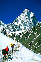 Three climbers trekking through partially melted snow on a path beneath Choltase in the Mount Everest region, Khumbu Himalaya, Nepal.