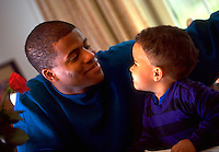 African-American father and son smiling at each other; affection; endearment, family activities, parents, children, Black child, man. Greg and James Churchman.