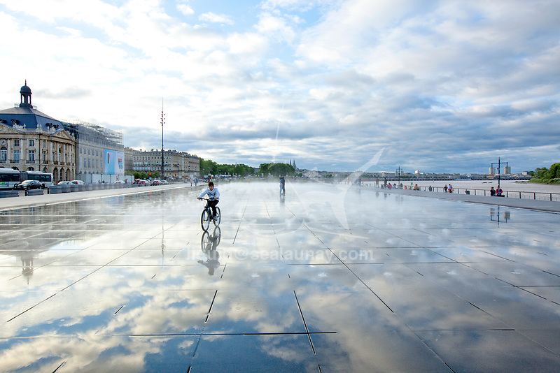 The Miroir d'eau (Water Mirror) or Miroir des Quais (Quay Mirror) in Bordeaux is the world's largest reflecting pool, covering 3,450 square metres (37,100 sq ft). <br /> Located across from Place de la Bourse, between Quai de la Douane and Quai Louis XVIII, this spectacular pool, designed by landscape artist Michel Corajoud, alternates a mirror effect and artificial misting in an extraordinary way. It is made of granite slabs covered by 2 cm of water. In summer, a system allows it to create fog every 15 minutes.<br /> Bordeaux is a port city on the Garonne in the Gironde department in Southwestern France.<br /> It is the capital of the Nouvelle-Aquitaine region, as well as the prefecture of the Gironde department.