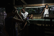 Ernesto Betasolo sits with his children and grand children in the kitchen of his house in Relocation Golden Valley in Barangay Pagkakaisa outside of Puerto Princesa, Palawan in the Philippines. <br /> Photo: Sanjit Das/Panos for Greenpeace