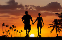 A couple in silhouette, walking into the sunset.