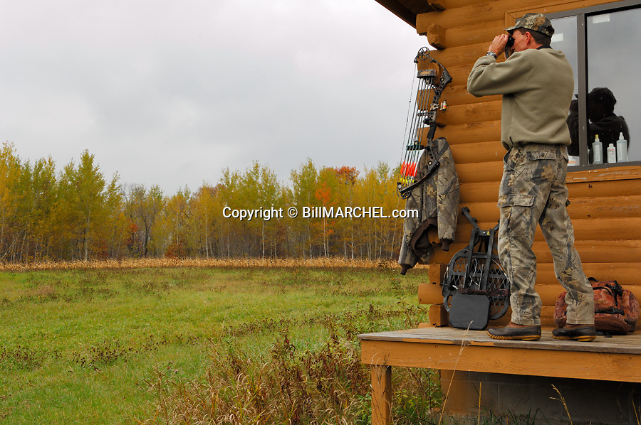 00105-042.05 Bowhunting (DIGITAL) Archer uses binoculars to watch for game from porch of hunting shack.  Backpack, tree stand.  H3L1
