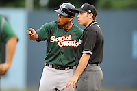 Savannah Sand Gnats manager Luis Rojas #19 discusses a play with first base umpire Mike Wiseman during a game against the Asheville Tourists at McCormick Field on July 30, 2013 in Asheville, North Carolina. The Sand Gnats won the game 9-5. (Tony Farlow/Four Seam Images)