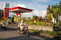 Jimbaran, Bali, Indonesia.  Male Motorcyclist and Cell Phone.