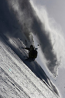 A snowboarder in action on a big mountain.