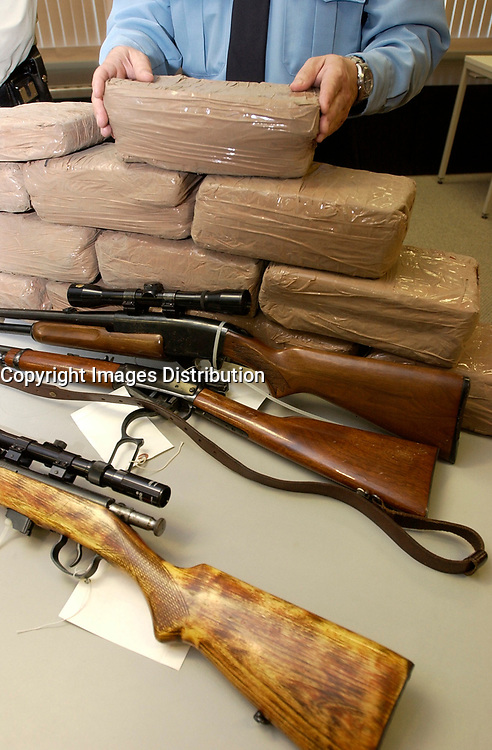 December 04,  2002, Montreal, Quebec, Canada; <br /> <br /> Policemen show drug, guns and money<br /> seized during a recent drug bust,to the medias,<br />  December 04, 2002 in Montreal, Canada.<br /> <br /> 15 people presumably involveld in a 2 billion Can $ drug deal, where arrested after a joint operation by the RCMP, Quebec Province and Montreal City Police.<br /> <br /> <br /> <br /> (Mandatory Credit: Photo by Sevy - Images Distribution (©) Copyright 2002 by Sevy<br /> <br /> NOTE :  D-1 H original JPEG, saved as Adobe 1998 RGB.<br />  Uncompressed and uncropped original  size file available on request.