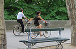 France, Paris.  <br /> A simple frame for a simple shot, trees and a bench contain the action.  Benches are everywhere, so I've learned to quickly incorporate them into my photos. Dog with couple riding bikes (velib), Paris, France.