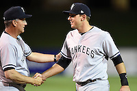 Tampa Yankees third baseman Eric Jagielo (20) shakes hands with manager Al Pedrique (13) after a game against the Lakeland Flying Tigers on April 3, 2014 at Joker Marchant Stadium in Lakeland, Florida.  Tampa defeated Lakeland 4-0.  (Mike Janes/Four Seam Images)