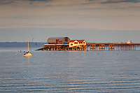 Pictured: Mumbles Head and the RNLI boathouse. Friday 16 April 2021<br /> Re: People enjoy an evening out after Covid-19 lockdown rules were relaxed, in Swansea Bay, Wales, UK.