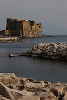 Napoli: A beautiful view from the coast of the Ovo castle (the castle of the Egg), enlightened by the sun. It is located on a little isle in a central position on the town's seafront, that is connected to the mainland by a short passage.