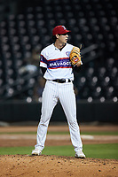 Winston-Salem Rayados relief pitcher Isaiah Carranza (20) looks to his catcher for the sign against the Llamas de Hickory at Truist Stadium on July 6, 2021 in Winston-Salem, North Carolina. (Brian Westerholt/Four Seam Images)