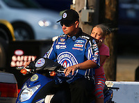 Aug. 1, 2014; Kent, WA, USA; NHRA funny car driver Robert Hight rides a scooter with daughter Autumn Hight during qualifying for the Northwest Nationals at Pacific Raceways. Mandatory Credit: Mark J. Rebilas-