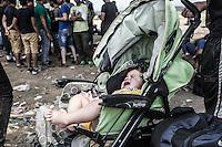 Un neonato in carrozzina piange, sullo sfondo gruppo di migranti<br /> A baby crying in a wheelchair , on the background a group of migrants