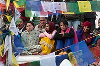 Bodhnath, Nepal.  Nepalese Crowd Watching Dancers at a Wedding Celebration, seen through lines of Prayer Flags.
