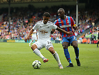 Pictured L-R: Kyle Naughton of Swansea is challenged by Yannick Bolasie of Crystal Palace<br /> Re: Premier League match between Crystal Palace and Swansea City at Selhurst Park on Sunday 24 May 2015 in London, England, UK