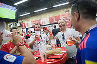 KAZAN, RUSSIA - June 24, 2018: Fans enjoy sharing a beer with each other during halftime of the 2018 FIFA World Cup group stage match between Poland and Colombia at Kazan Arena.