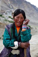 "China started building a controversial 67-mile ""paved highway fenced with undulating guardrails"" to Mount Qomolangma, known in the west as Mount Everest, to help facilitate next year's Olympic Games torch relay./// A young woman works with a shovel building the road to Everest Base Camp.<br /> Tibet, China<br /> July, 2007"