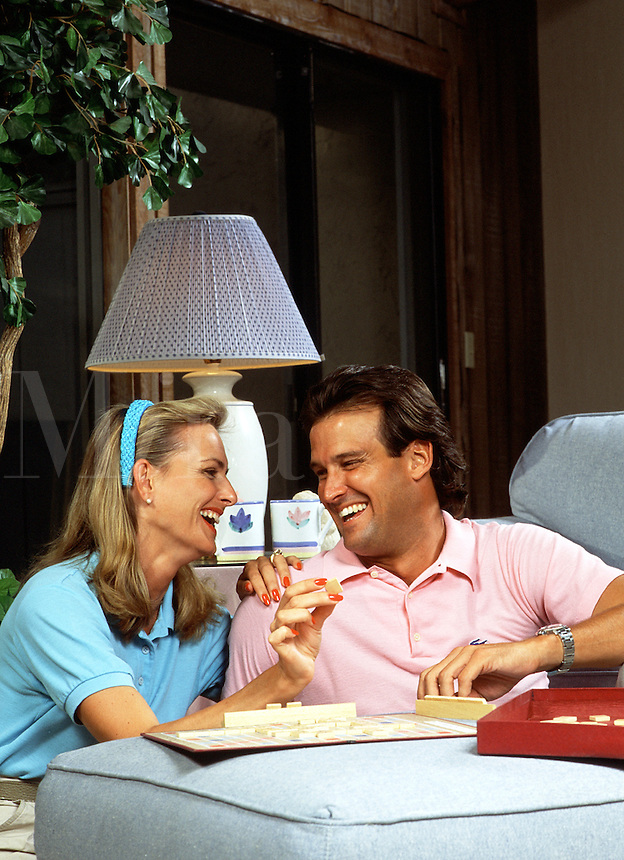 A smiling young couple has fun playing a board game.