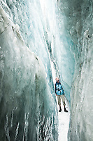 Man walking through deep and beautiful ice crevasse on Franz Josef Glacier - Westland National Park, West Coast, New Zealand