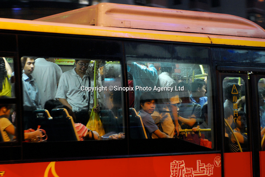 Commuters are pack into buses on their way home from work in the business district in Guangzhou, China. .27 May 2006.