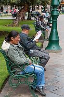 Peru, Cusco.  Peruvians Resting on Benches in the Plaza de Armas.