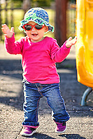A pretty little girl with <br /> red glasses and blue hat having fun