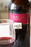 Wine glasses in the tasting room. Bottle of Vranac Vrhunsko Suho Vino red wine. Detail of label with picture of winery building. Vinarija Citluk winery in Citluk near Mostar, part of Hercegovina Vino, Mostar. Federation Bosne i Hercegovine. Bosnia Herzegovina, Europe.