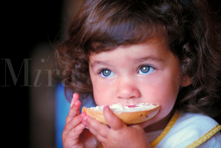 young girl eating bagel