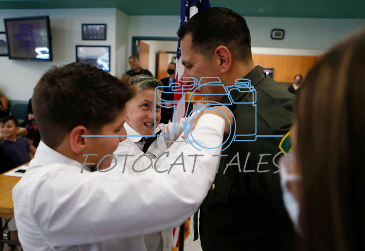 Cruz and Chase Gonzales pin Lieutenant bars on their dad, Daniel Gonzales, during a promotion ceremony at Carson City Sheriff's Office, in Carson City, Nev., on Thursday, July 2, 2020. <br /> Photo by Cathleen Allison