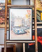 BNPS.co.uk (01202 558833)<br /> Pic: MaxWillcock/BNPS<br /> <br /> Pictured: A motoring poster printed for the 1994 Tour de Auto featuring an image of Michael Wright's watercolour of the Tour de France Automobile 1971 race, in the Dreweatts Donnington Priory saleroom.<br /> <br /> A glamorous collection of early French motorsport posters has emerged for sale with a British auction house for £25,000.<br /> <br /> The earliest examples date from 1900 showing well-heeled Parisians chauffeured in vintage cars on the capital's streets.<br /> <br /> The vehicles are flanked by marching bands with passengers in their finest clothes to reinforce the element of prestige.<br /> <br /> There is a striking 1902 French poster of a British Mulberry car in the Scottish Highlands, while another celebrates the 1934 Grand Parade Vichy.