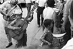 Mazatlan Mexico. Children busking in the street, brother, young sibling collecting in his hat and playing a simple wooden percussion block. Mexican state of Sinaloa 1973.