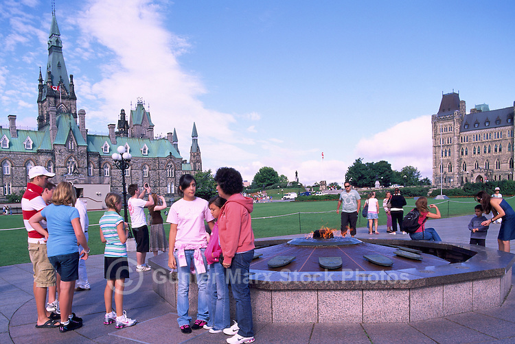 "Parliament Buildings on Parliament Hill, in the City of Ottawa, Ontario, Canada - Tourists visiting ""Centennial Flame"" (lit 1967) in front of West Block (built 1865) and Centre Block (built 1865 - 1927)"