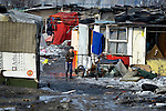 A boy walks through an illegal Roma settlement in Belgrade, Serbia. The families that live here, many of whom survive from recycling cardboard and other materials, are under constant threat of eviction in order to make way for new high-rise office buildings. Note: residents of this settlement were forcibly evicted in April 2012, two months after this photo. Many were relocated in metal shipping containers at the edge of the city.