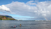 Surfers in Hanalei Bay see a rainbow off of Kaua'i.