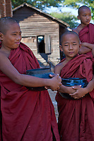 Myanmar, Burma.  Bagan.  Young Novice Monks Holding their Begging Bowls.