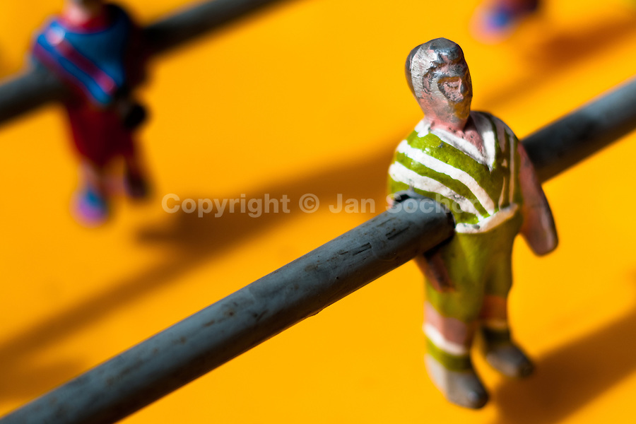 A table football player figure, with a painted green and white shirt, is seen inside the table football box on the street of Olmedo, a small village in the mountains of Ecuador, 27 June 2010. Table football, also known as futbolin in Latin America, is a widely popular table-top game in Ecuador. During the annual fairs, the rusty old outdoor-designed tables, fully ocuppied by excited children, may be found on all public places, particularly on the squares and in the parks. Human players use figures mounted on rotating bars to kick the small plastic ball into the opposing goal. Each team of 1 or 2 human players controls 4 rows on its side of the table. The game ends when one team scores a predetermined number of goals. In 2002, the International Table Soccer Federation (ITSF) was established to promote the sport of table football.