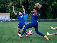 CLEVELAND, OH - SEPTEMBER 14: Alex Morgan nutmegs Casey Krueger of the United States during a training session at the training fields on September 14, 2021 in Cleveland, Ohio.