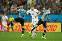 Rickie Lambert of England takes on Egidio Arevalo and Jose Gimenez of Uruguay