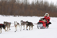 Sitting on his sled chair with two dogs *in the basket,* Fabrizio Lovati runs down the Kuskokwim river shortly before McGrath on Wednesday during Iditarod 2008
