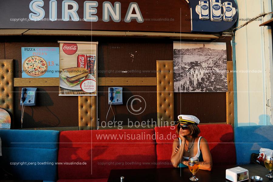 TURKEY Istanbul, woman with captain hat drinks Efes beer in Pub under bridge over Golden Horn/ TUERKEI Istanbul, Frau mit Kapitaens Muetze trinkt Efes Bier