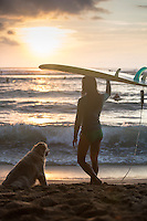 Young woman prepares to go surfing at sunset while her loyal dog waits on the beach at Puaena Point, O'ahu.